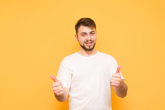 Man wears a white t-shirt, shows a thumbs up and looks at the camera, isolated on a yellow
