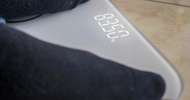 사람은 디지털 저울로 자신의 무게를 잰다. 전자 디스플레이에 선택적 초점.