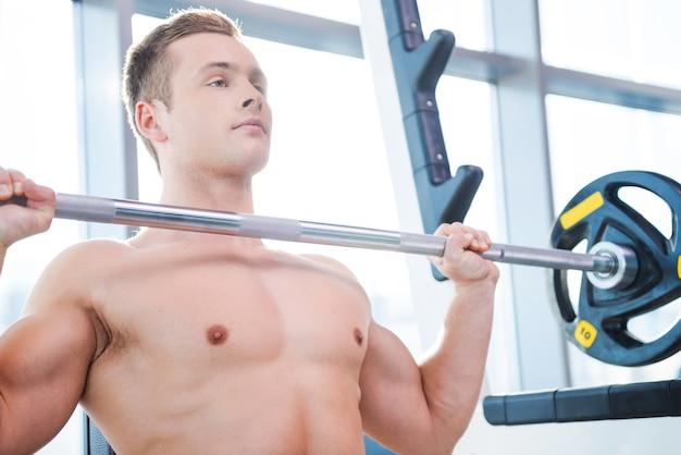 男の重量挙げ。ベンチプレスで働いている集中した若い筋肉の男
