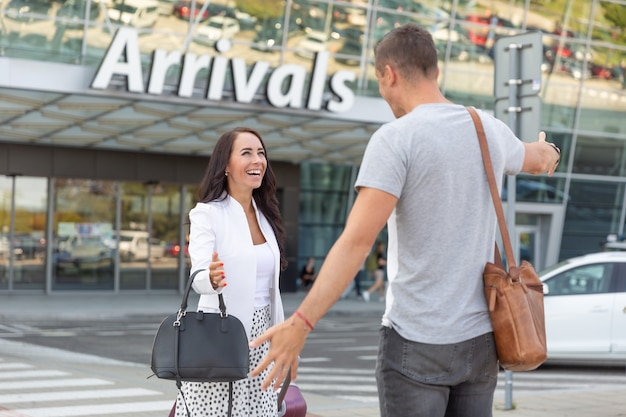 A man welcomes his happy wife after she exits the arrival hall at the airport.
