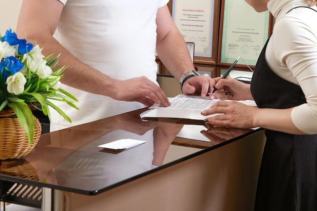 オフィスの受付で若い女性のクライアントを歓迎する男性