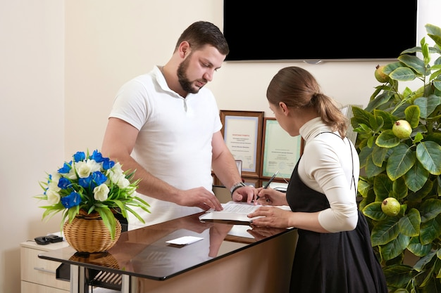 Man welcoming young woman client at office reception desk