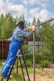 溶接マスク、建設用ユニフォーム、保護手袋を着用した男性溶接工が、通りの建設現場で金属を調理します。夏の日のカントリーハウスの近くにパビリオン、パーゴラを建設。
