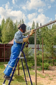 Man welder in a welding mask, construction uniform and protective gloves cooks metal on a street construction site. construction of a pavilion, pergola near a country house on a summer day.