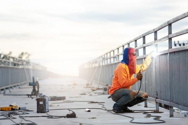Человек сварщик работает на строительстве моста.