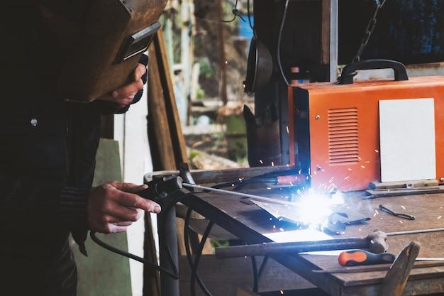Man welding old shovel, close up.