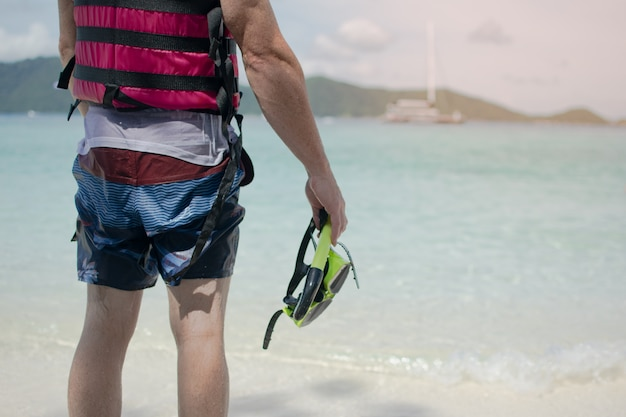 Man in wet outfit facing to the sea, holding snorkeling mask after finished snorkeling in the island