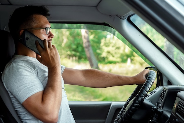 A man at the wheel holding a smartphone in his hand