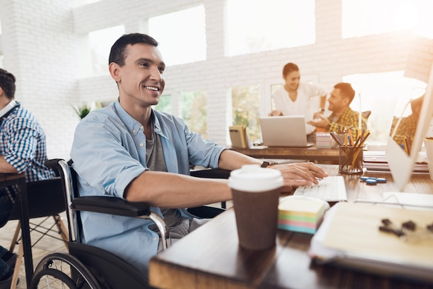 A man in a wheelchair is working in a bright office.
