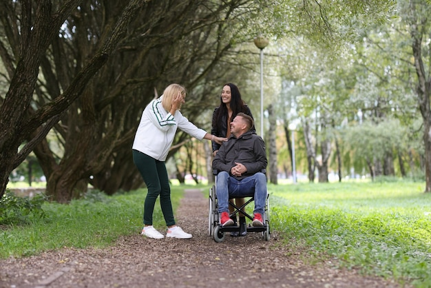 Man in wheelchair and laughing female friends walking in park rehabilitation of disabled people