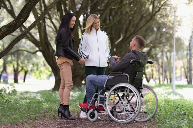 Man in wheelchair and laughing woman chatting in park psychological support friends for