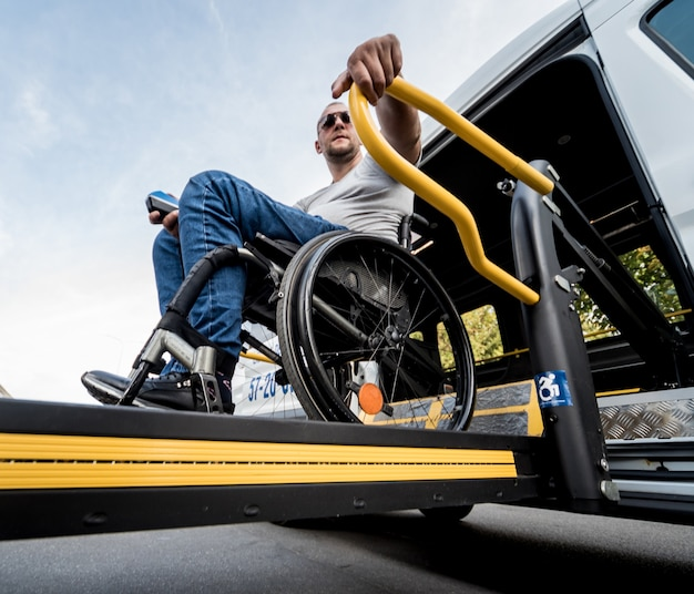 A man in a wheelchair on a lift of a specialized vehicle for people with disabilities.