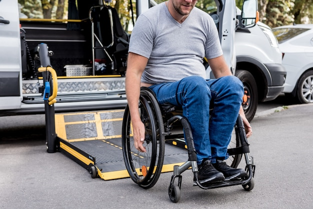A man in a wheelchair on a lift of a vehicle for people with disabilities.