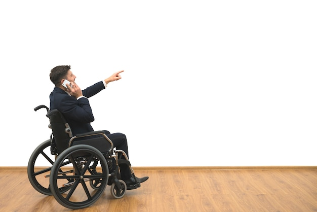 The man in a wheelchair phones and gestures on the white wall background