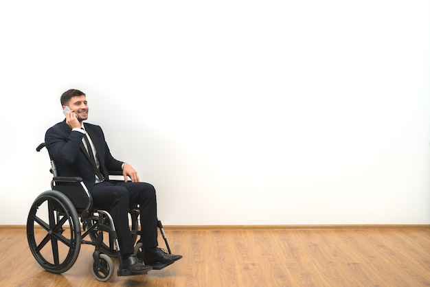 The man in a wheelchair phones on the white wall background