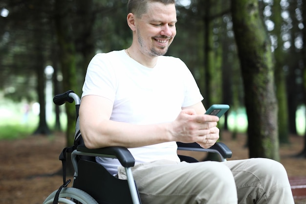 Man in wheelchair sits holding smartphone in his hand and smile