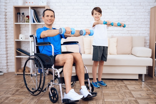 Man in wheelchair and son with dumbbells in hands.