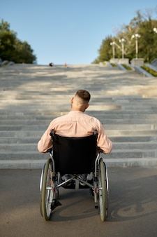 Man in wheelchair at the stairs, back view