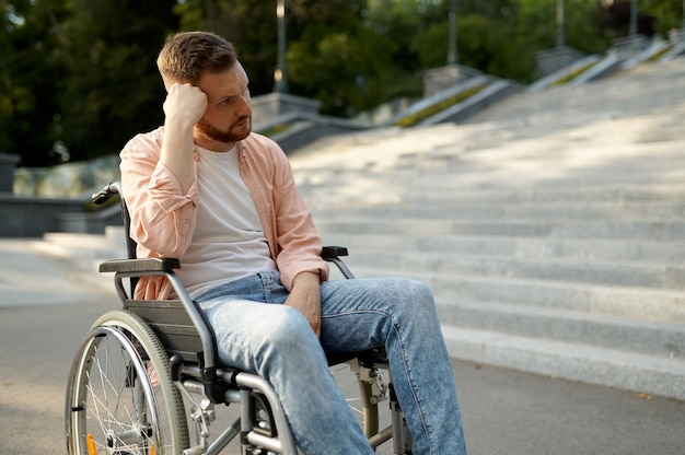 Man in wheelchair at the stairs, handicap problem