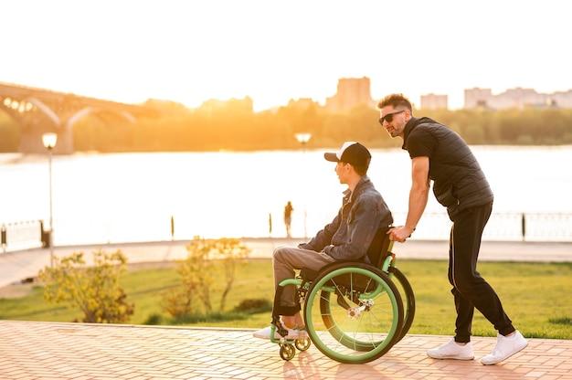 A man in a wheelchair walks with his friend man walking with disabled friend in wheelchair at park