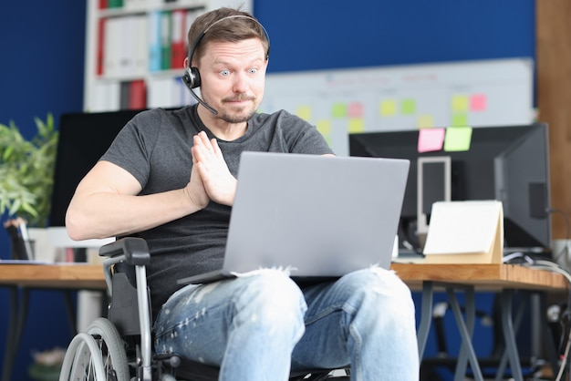 Man in wheelchair and wearing headphones with microphone works on laptop