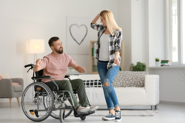 Man in wheelchair with beautiful woman dancing at home