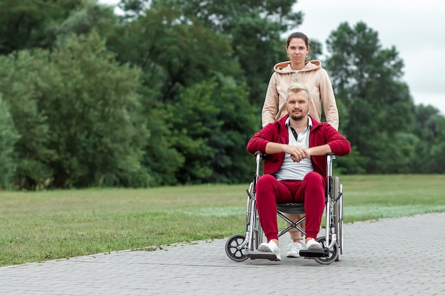 A man on a wheelchair with a girl spend time in the park. the man is disabled. the concept of a wheelchair, disabled person, full life, paralyzed, disabled person, health care.