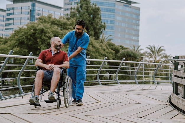A man in wheelchair with his assistant outdoor