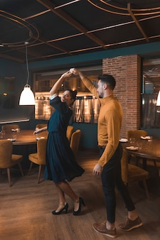Man whirling cheerful woman in restaurant