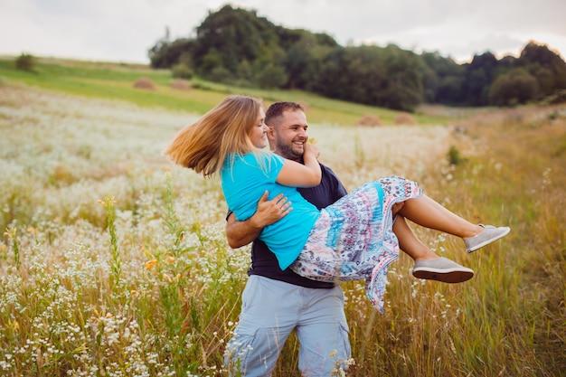 Человек whirls блондинка женщина на руках, стоя на поле