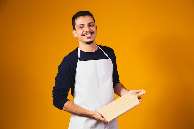 Man in white apron holding a chopping board.