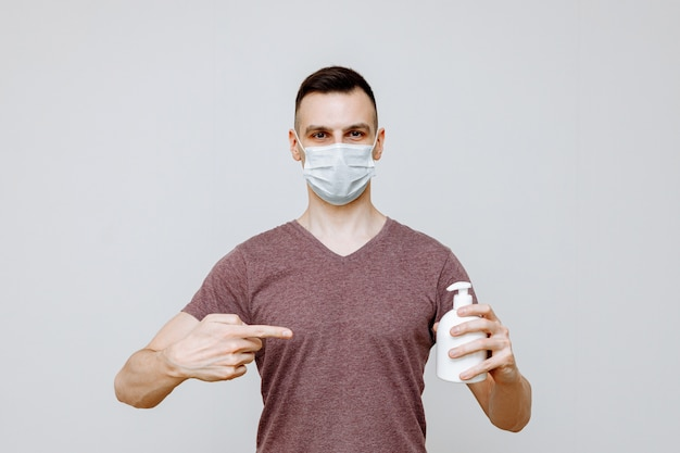 A man on a white background wearing a hygiene mask uses a hand sanitizer to prevent infection with flu, colds, or coronavirus.