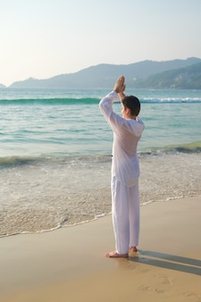 Man in white clothing holds his hands in a prayer gesture and practices yoga meditation