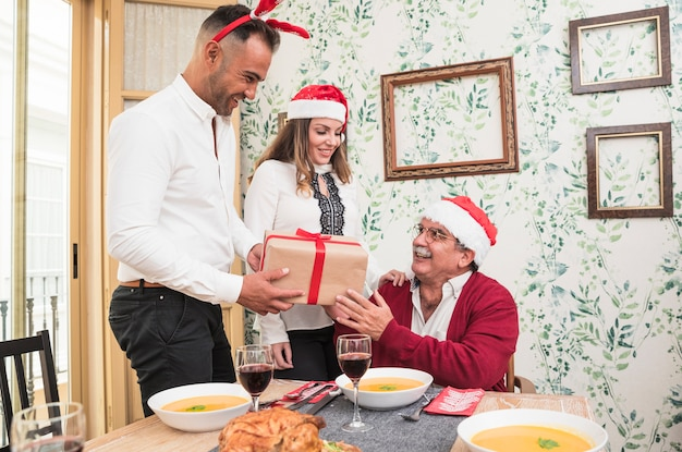 Man in white giving gift box to happy old man