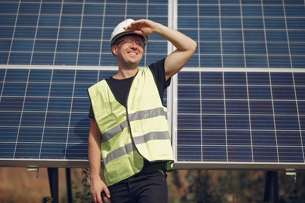 Man in a white helmet near a solar panel
