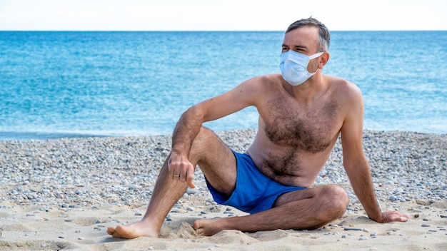 Un uomo in maschera medica bianca al mare