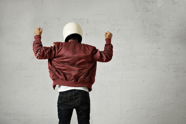 Man in white motorcycle helmet and burgundy pilot jacket shot from the back with both fists up in the air with shaka gesture against white wall background.