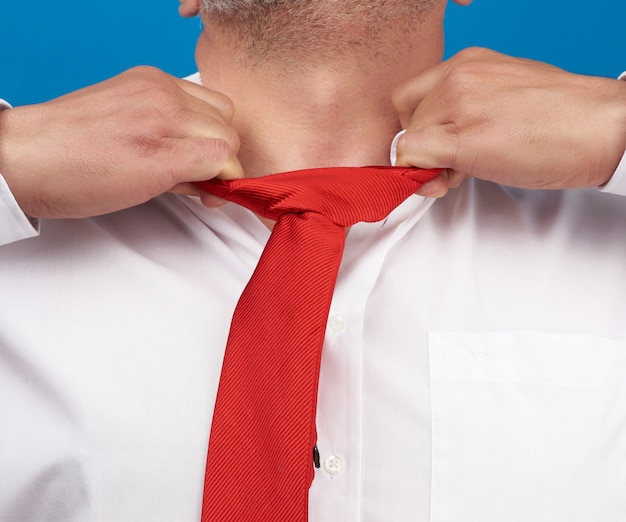 Man in a white office shirt tears off a red satin tie from his neck