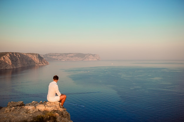 Man in white outdoor on edge of cliff enjoy the view on mountain top rock