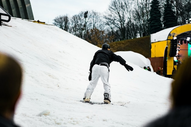 Man in a white pants and black jacket moving out from the slope on a snowboard.