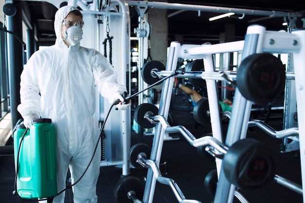 Man in white protection suit disinfecting and fitness equipment and weights to stop spreading highly contagious corona virus
