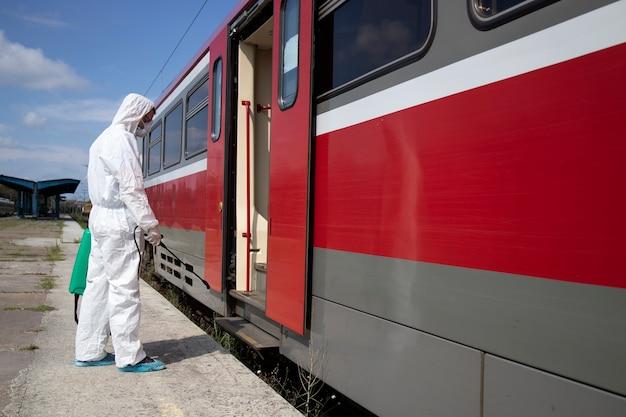 Uomo in tuta di protezione bianca che disinfetta e igienizza l'esterno del treno della metropolitana per fermare la diffusione del virus corona altamente contagioso