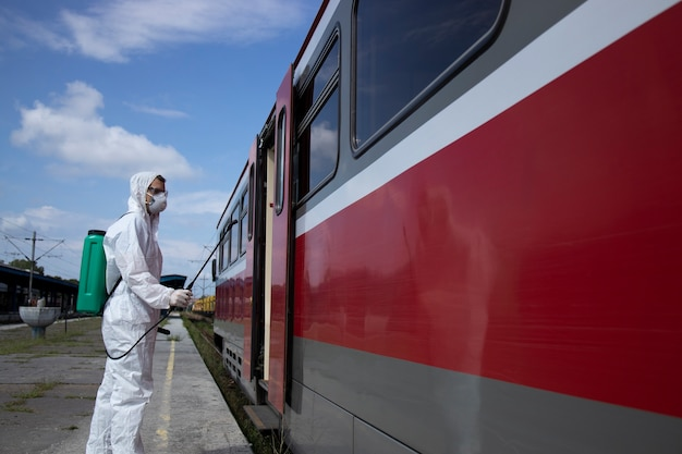 Man in white protection suit disinfecting and sanitizing subway train exterior to stop spreading highly contagious corona virus