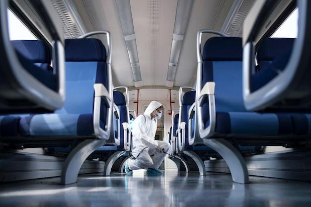 Uomo in tuta di protezione bianca che disinfetta e igienizza l'interno del treno della metropolitana per fermare la diffusione del virus corona altamente contagioso