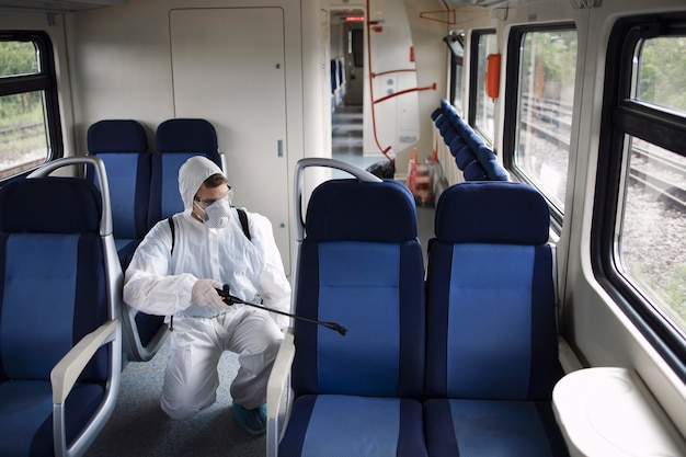 Man in white protection suit disinfecting and sanitizing subway train interior to stop spreading highly contagious corona virus