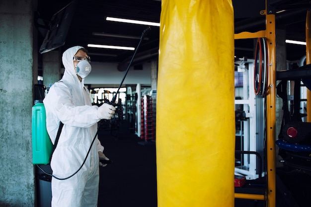 Man in white protection suit disinfecting and spraying fitness equipment to stop spreading highly contagious corona virus