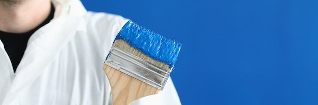 Man in white protective suit hold paintbrush in his hand. wooden brush smeared with blue paint against blue wall.