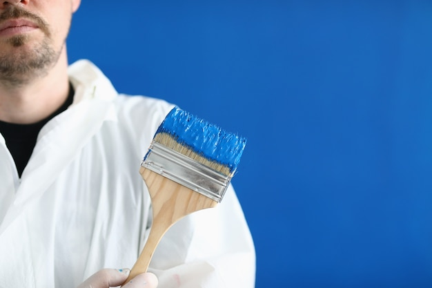Man in white protective suit hold paintbrush in his hand.