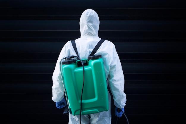 Uomo in tuta protettiva bianca con serbatoio per irrorazione e disinfezione