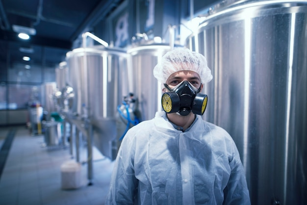 Man in white protective uniform with hairnet and protective mask handling hazardous chemicals